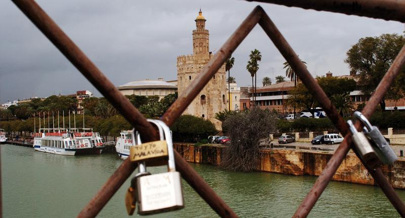 Los enamorados ponen candados y lanzan las llaves al rio emulando la novela de Federico Moccia. Al fondo La Torre del Oro